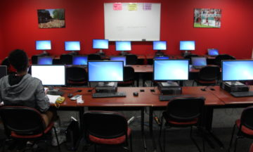 A lone student uses a computer in a computer lab