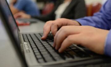Hands on a laptop keyboard.
