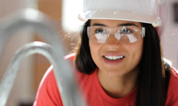 A student in a hard hat works in a lab